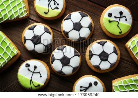 Tasty football cookies on wooden background