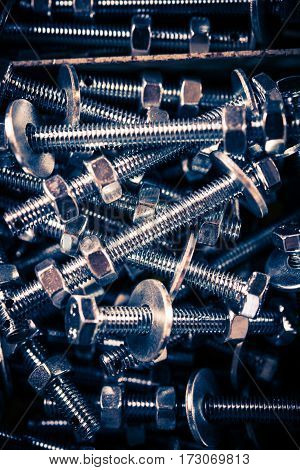 Stainless Steel Screws Closeup Vertical Photo. Dark colors.