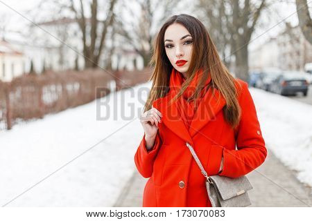 Pretty Young Woman In A Fashionable Red Coat And Scarf Walking On A Winter City