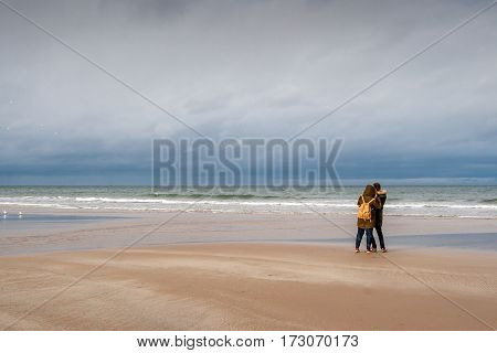 A young couple looking out to the North Sea: Bamburgh Beach, Northumberland, England, UK. March 15 2016.