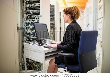 Technician working on computer in server room