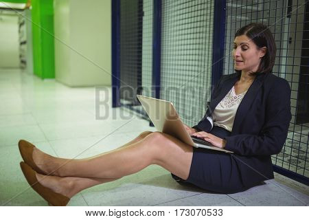 Technician siting on floor and using laptop in server room