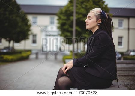 Businesswoman with eyes closed relaxing in office campus