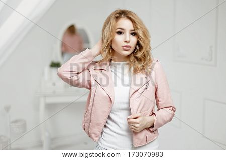 Beautiful Young Blonde Girl In Stylish Leather Jacket Posing In A White Room