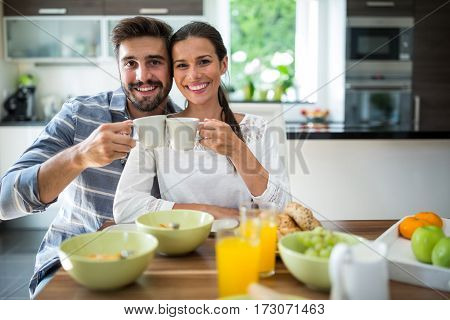 Portrait of couple toasting a cup of coffee while having breakfast at home