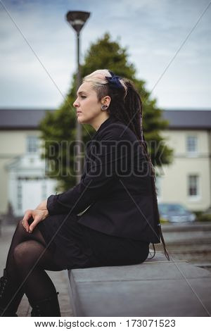 Thoughtful businesswoman relaxing in office campus