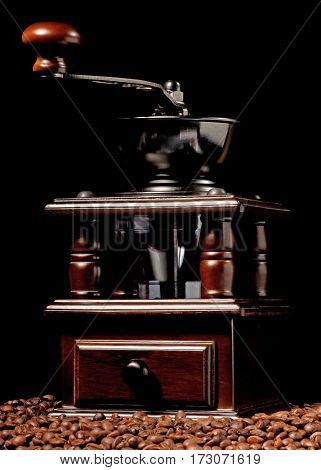 Manual coffee grinder with coffee beans on black background