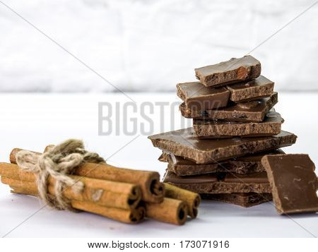 milk chocolate with cinnamon, raisins on white background