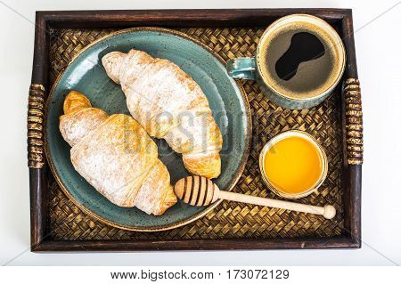 Croissant, honey and espresso in blue vintage bowl on wooden tray. Studio Photo