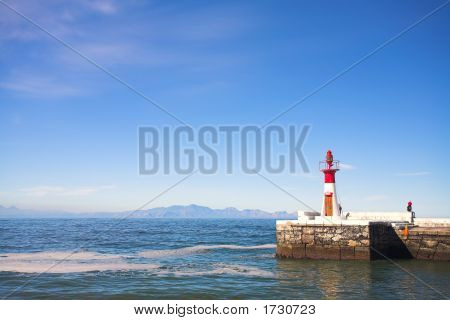 The left harbor entrance (red) lighthouse at Kalk bay harbor in the Western Cape South Africa. A sunny summer day with clear blue skies and calm water. poster