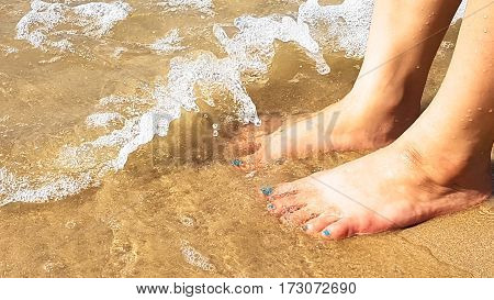 Woman's foot put on the sand beach with clearly sea wave