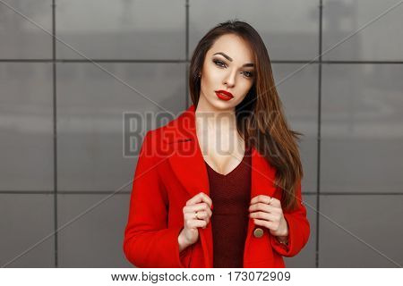 Beautiful Woman In A Red Coat Near The Gray Wall