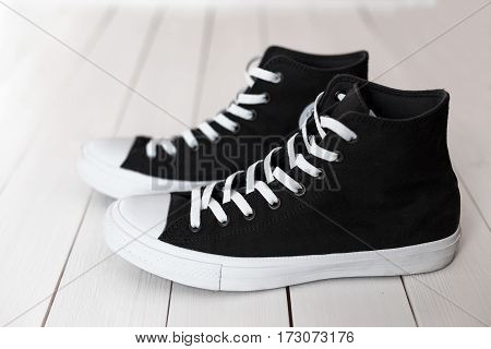 Stylish Black Sneakers On The Wooden Table