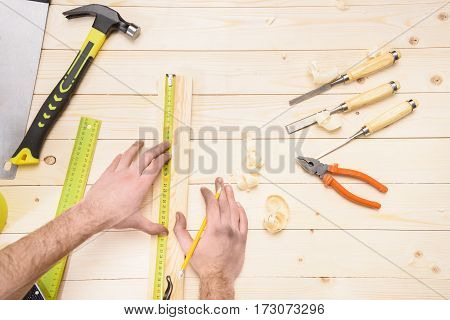 Partial top view of carpenter measuring wooden plank with tape measure in workshop