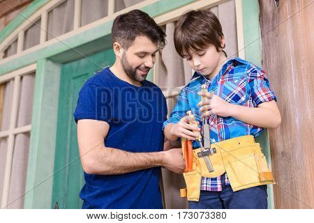 Smiling father looking at son standing in tool belt and holding tools