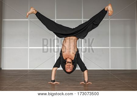Handsome male athlete standing on hands. Dance man