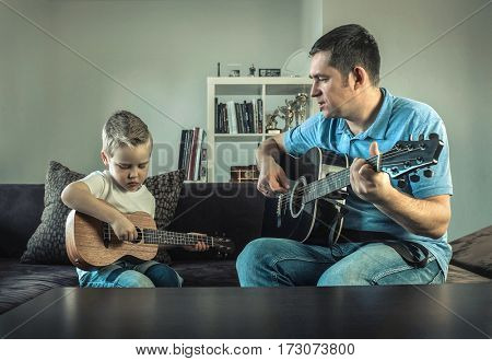 Father teaching his son to play on guitar at home. Son play on ukulele - hawaiian guitar.