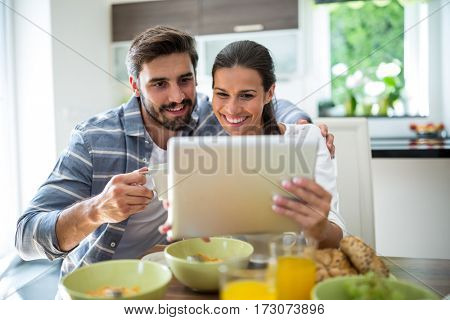 Couple using digital tablet while having breakfast at home