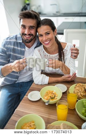 Portrait of smiling couple having breakfast at home