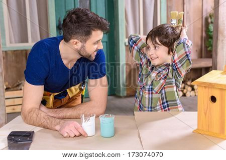 Happy father and son making birdhouse and looking at each other in workshop