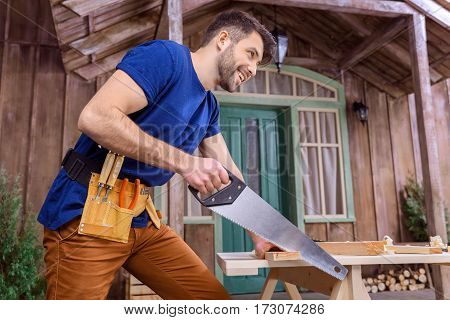 Low angle view of smiling bearded carpenter in tool belt sawing wooden plank on porch