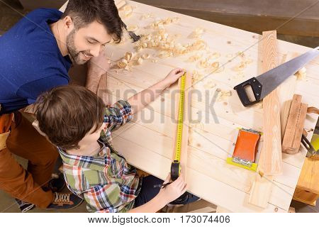 High angle view of happy father looking at son measuring wooden plank with measure tape