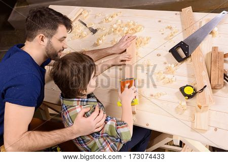 Elevated view of father and son planing wooden plank with hand plane
