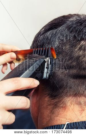 Brunette man getting a haircut by a professional hairdresser using comb and grooming machine. Closeup man having a haircut with a hair clippers. The hands of barber making haircut to man in barbershop