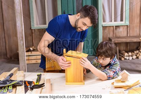 Concentrated father and son making wooden birdhouse together