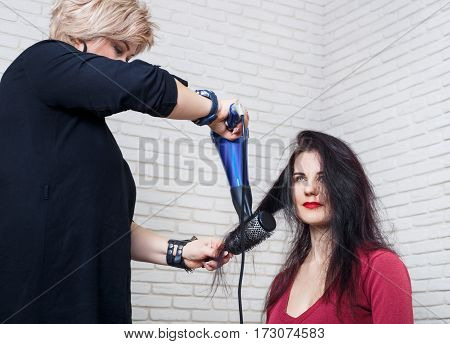 Drying hair with hair dryer and round brush. Young woman and hairdresser with fan making hot styling at hair salon. Hair drying at salon