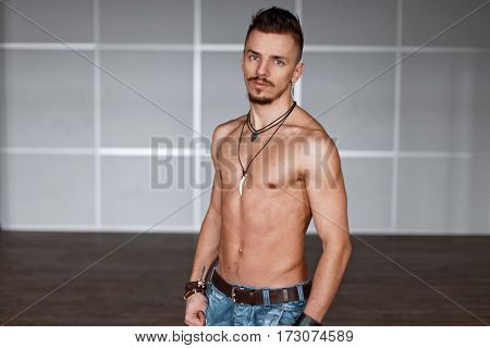 Stylish Handsome Man With Naked Torso With Hair And Beard Near Gray Wall.