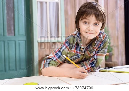 portrait of smiling boy with pencil in hands looking to camera