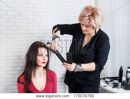 Professional hairdresser middle aged woman straightening long hair with hair irons in beauty salon. Young woman is getting her hair equalized. Stylist straightening hair of a client