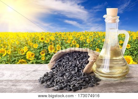 Sunflower oil in glass bottle and seeds on wooden table with blossom field on the background. Sunflower field with blue sky and sun. Photo with copy space. Agriculture and harvest concept
