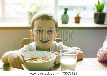 Little Boy Enjoying Bowl Of Cereal
