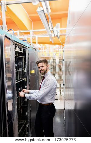 Portrait of technician examining server in server room