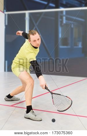 young caucasian squash player hitting a ball in a squash court. Squash player in action. Man playing match of squash. Sports activities squash