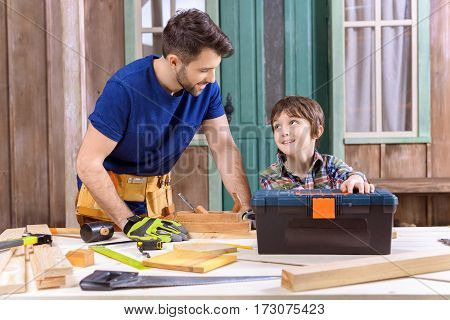 portrait of son helping father working with wooden planks on porch