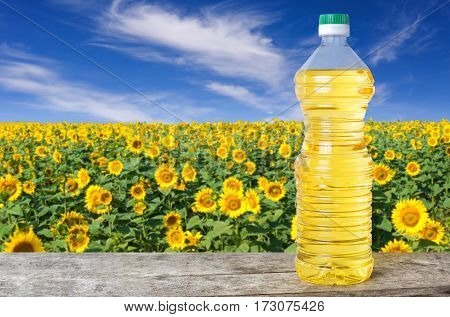 Sunflower oil in plastic bottle on wooden table with blossom field on the background. Sunflower field with blue sky. Photo with copy space area for a text. Agriculture and harvest concept