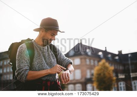 Young man wearing tourist bag and hat looking at his smart watch. Tourist smiling looking at his watch with sunlight in the background.