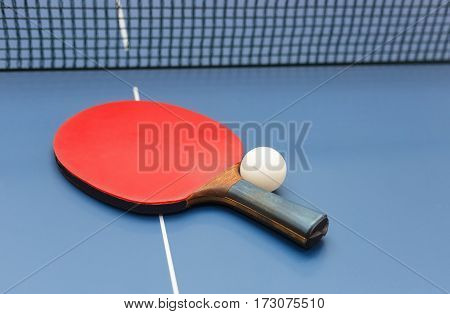 Table tennis racket, white ball and net on a on blue board. Equipment for table tennis. Ping pong. Indoor games