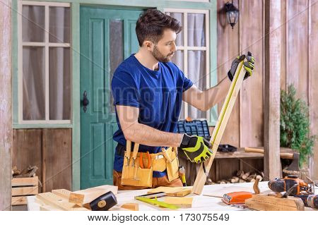 side view of concentrated carpenter taking measures of wooden plank on porch