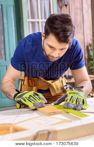portrait of concentrated carpenter in protective gloves measuring cut of wooden plank
