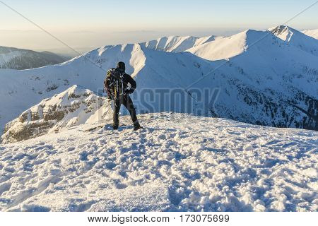 Boy With The Backpack And Ice Axes In The Winter In The Mountains.