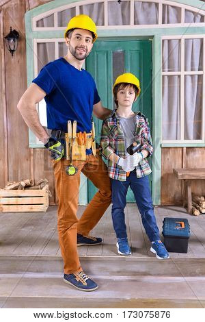 father and son in helmets with building tools standing on porch