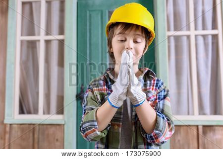 portrait of smiling boy in helmet standing on porch and looking at hands in protective gloves