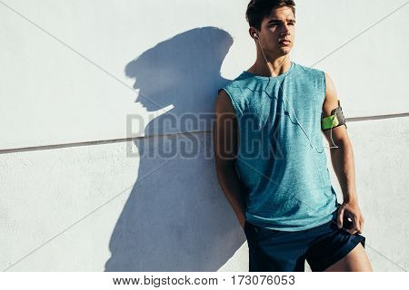Shot of fitness man leaning to a wall and looking away. Male runner relaxing after workout.