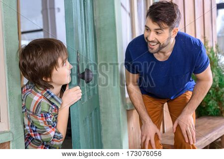 side view of smiling father and son playing hide and seek at home