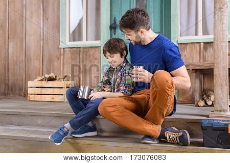 smiling man and boy with metal cups of tea sitting on porch