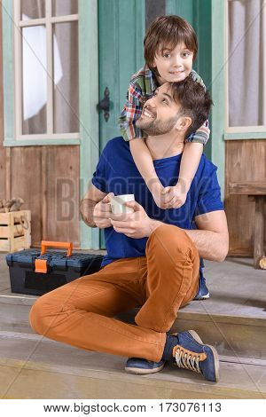 man sitting on porch with tea cup while smiling boy hugging him and looking to camera
